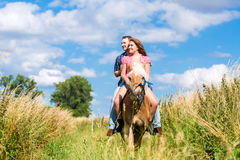 Couple riding in summer meadow Royalty Free Stock Image