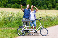 Couple riding tandem bike together in the country Royalty Free Stock Photography
