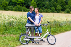 Couple riding tandem bike together in the country Royalty Free Stock Image