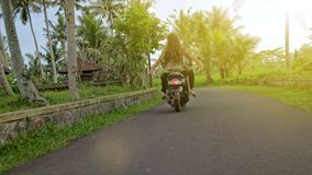 Happy couple tripping by motorcycle on tropical road at sunset time. Outdoor shot of young couple riding motorbike. Man