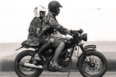 Couple riding a vintage motorbike. royalty free stock image