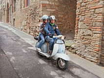 Couple riding a vintage scooter Lambretta Royalty Free Stock Image