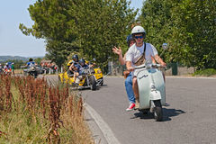 Couple riding vintage scooter Vespa Stock Photos