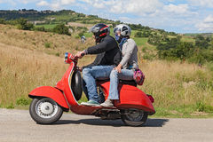 Couple riding vintage scooter Vespa Royalty Free Stock Images