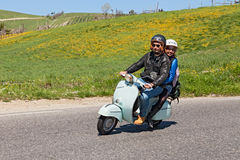 Couple riding a vintage scooter Royalty Free Stock Photography