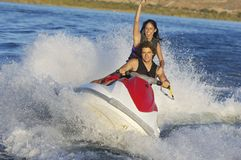 Couple Riding Water Scooter Stock Image