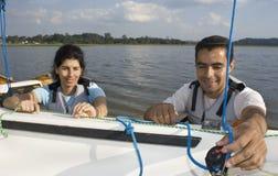Couple Rigging Sails on Sailboat  - Horizontal. Man and woman smiling while rigging sails on sailboat. Horizontally framed photo Royalty Free Stock Image