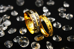 Couple Ring - Reflection. Reflection of bride and groom on a pair of gold couple ring surrounded with many crystals Royalty Free Stock Photo