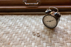 Couple ring on weave table with alarm clock Stock Image