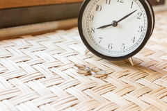 Couple ring on weave table with clock Royalty Free Stock Images