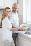 Couple rinsing vegetables at the sink Stock Photo