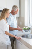 Couple rinsing vegetables at the sink Royalty Free Stock Photos