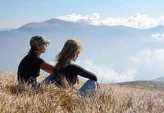 Couple On Rising. Young womans relaxing on mountain meadow Stock Photo