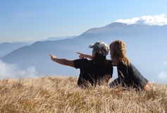 Couple On Rising. Young womans relaxing on mountain meadow Stock Photos
