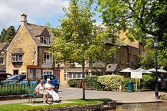Couple by river, Bourton on the Water. Couple sitting on a bench alongside the River Windrush in the village centre, Bourton on the Water, Gloucestershire stock image