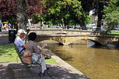 Couple by river, Bourton on the Water. Royalty Free Stock Images