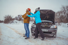 Couple on the road with broken car Stock Photography