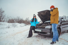 Couple on the road with broken car Royalty Free Stock Image