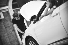 Couple on the road having problem with a car. royalty free stock photos
