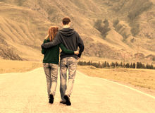 Couple road romance. Young happy romantic couple (caucasian men and woman) walking along the asphalt road among beautiful mountain area (Altai region, Russia) Stock Image