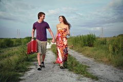 Couple on road with suitcase. Couple running together, holding hands and carrying a suitcase Stock Photography
