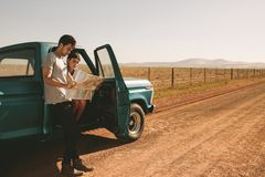 Couple on a road trip looking at map for navigation. Couple looking at a map for navigation while on a road trip. Man and women using a map to navigate through Stock Image