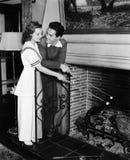 Couple roasting marshmallows over fireplace Royalty Free Stock Image