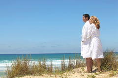 Couple in robes on ta beach Royalty Free Stock Image