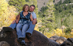 Couple on Rock. With Fall colors all around, this happy young couple in casual dress smile for your message. Room for your text Stock Photo