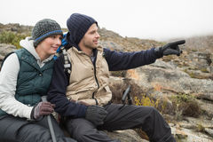 Couple on rock with trekking poles while on a hike Royalty Free Stock Photography
