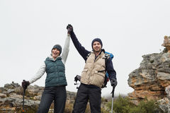 Couple on rocky landscape with hands raised against sky Stock Photo
