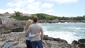 Couple on the rocky shore. Boy and girl hugging on the rocks. To stock footage