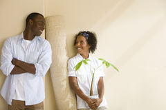 Couple with rolled carpet and potted plant Royalty Free Stock Photos