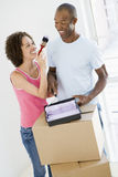 Couple with roller and paint in new home Stock Image