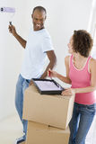 Couple with roller and paint in new home Stock Photos