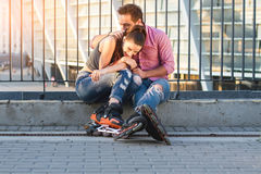 Couple of rollerbladers sitting. Royalty Free Stock Photos