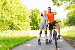 Couple on rollerblades and bike showing thumbs up Stock Image