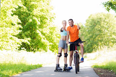 Couple on rollerblades and bike showing thumbs up Royalty Free Stock Image