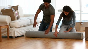 Couple rolling a carpet stock video