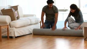 Couple rolling a carpet