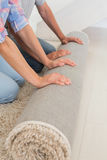 Couple rolling out new rug Royalty Free Stock Images