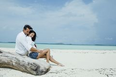 Romantic couple on beach. Romantic young couple sat on log on white sandy beach, sea in background Royalty Free Stock Photography