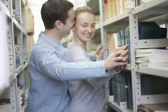 Couple Romancing In Library. Loving young couple romancing in library Stock Image
