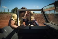 Couple romancing together behind a car. On a sunny day Royalty Free Stock Photography