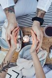 Beautiful couple holds hands over candle light. Couple on romantic date in chic, bohemian, provence style picnic, warm their hands next to candle light, concept Stock Image