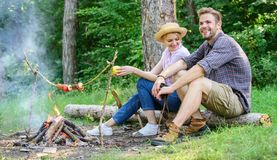 Couple romantic date near bonfire in forest. Couple relaxing sit on log having snacks. Hike picnic date. Family enjoy stock photography