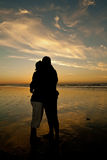Couple in romantic embrace. Silhouette of a romantic couple embracing each other in the golden light of sunset on a deserted beach stock photo