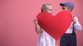 Couple of romantic kids hiding behind red heart cutout and kissing, first love