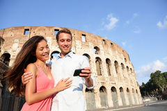 Couple in Rome by Colosseum using smart phone Royalty Free Stock Photography