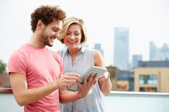 Couple On Roof Terrace Using Digital Tablet Stock Photography